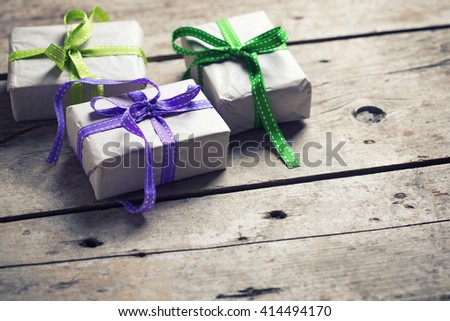 Festive gift boxes with presents  on aged wooden background. Selective focus. Place for text. Toned image. - stock photo