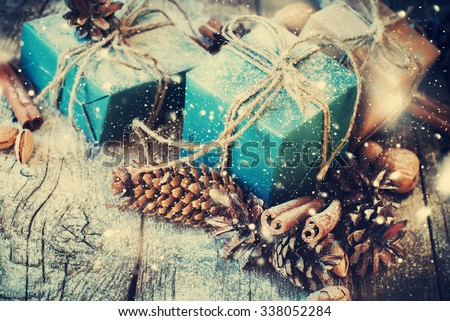 Festive Gifts Decorated with Linen Cord, Cinnamon, Pine cones, Walnuts. Toned image. Snow Drawn - stock photo