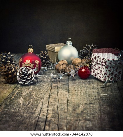 Festive Gifts with Boxes, Baubles, Pine Cones, Walnuts on Wooden Background. Christmas Decoration with black Background.