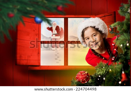 Festive girl looking from behind christmas tree against festive fir branch with baubles - stock photo