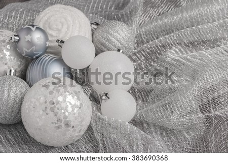 Festive glitter christmas balls decorations on metalic fabric texture. Seasonal winter holidays. Top view with copy space - stock photo