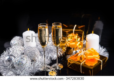 Festive Glittering Christmas Still Life - Pocket Watch, Glasses of Champagne, Gifts Wrapped in Gold Paper, Candle with Flame, and Silver Decorations on Black Background - stock photo