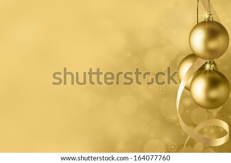 Festive gold Christmas baubles and spiral streamer on the right. Circles of bokeh glow, sparkling stars and snowflakes in the background fading towards solid colour copy space on the left side. - stock photo