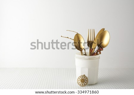 Festive golden cutlery knife and fork spoon in a white bottle on a light background - stock photo
