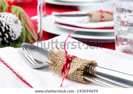Festive holiday dinner setting, white napkins, crockery, cutlery tied with hessian ribbon detail - stock photo