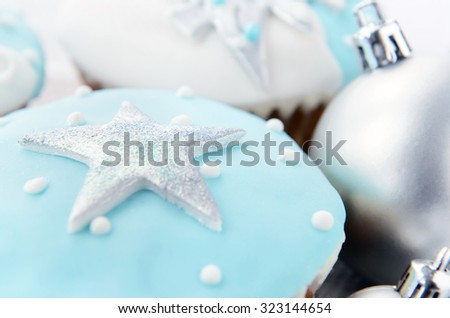Festive holiday frosty icy white christmas theme cupcakes with silver ornament baubles - stock photo