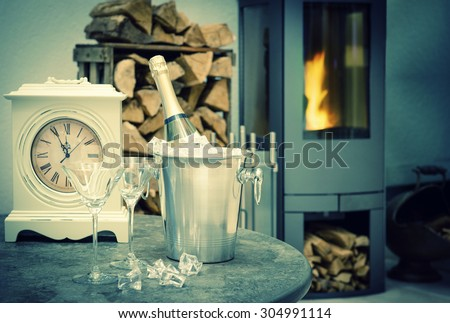 Festive home interior with champagne, vintage clock and fireplace. Retro style toned picture. Selective focus - stock photo