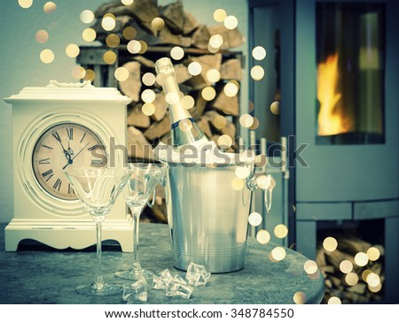 Festive home interior with champagne, vintage clock and fireplace. Retro style toned picture with bokeh lights effect - stock photo
