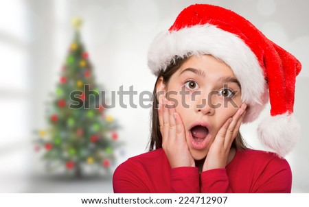 Festive little girl looking surprised against blurry christmas tree in room