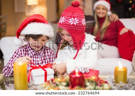 Festive little girl opening a gift with brother at home in the living room - stock photo