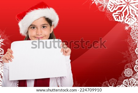 Festive little girl showing card against christmas themed snow flake frame - stock photo