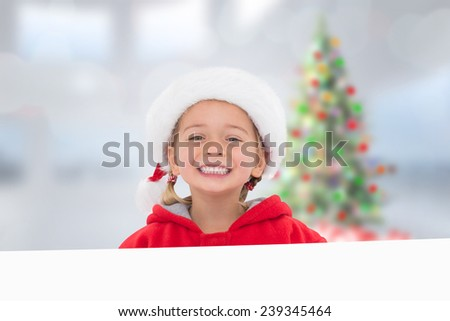 Festive little girl showing poster against blurry christmas tree in room - stock photo