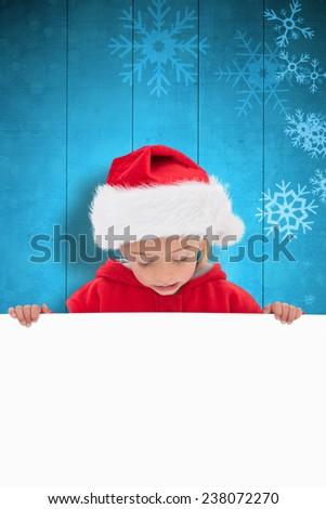 Festive little girl showing poster against snowflake pattern on blue planks - stock photo
