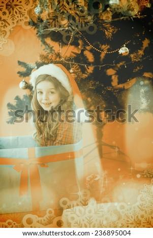 Festive little girl sitting in large gift against candle burning against festive background - stock photo