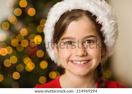 Festive little girl smiling at camera at home in the living room