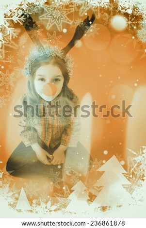 Festive little girl wearing red nose against candle burning against festive background - stock photo