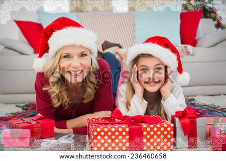 Festive little girl with mother surrounded by gifts against snowflake frame - stock photo