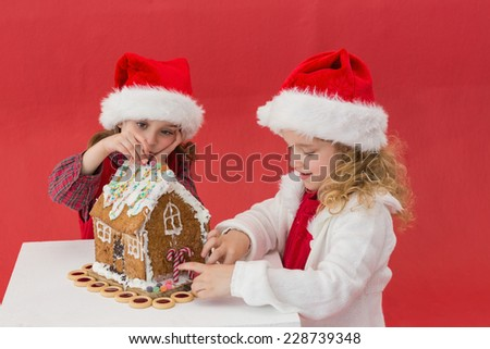 Festive little girls making a gingerbread house on red background - stock photo