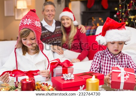 Festive little siblings opening a gift in front of their parents at home in the living room