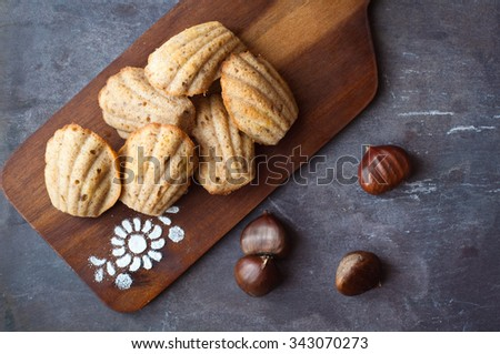 Festive madeleines baked with chestnut and served on a wooden board for a Christmas treat. A traditional French tea cake formed in a distinctive shell shape.