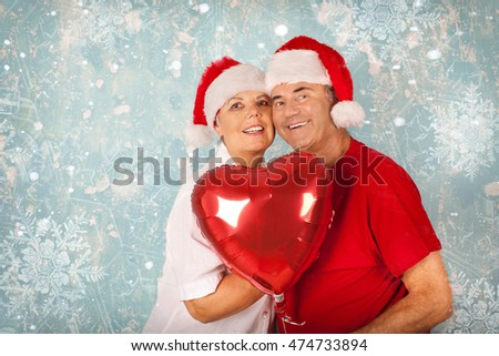 Festive mature couple holding a heart balloon against winter Background, Christmas concept
