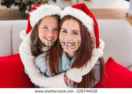 Festive mother and daughter on the couch at home in the living room