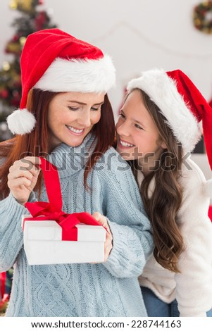 Festive mother and daughter on the couch with gift at home in the living room
