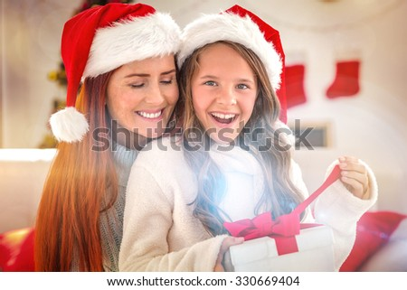 Festive mother and daughter on the couch with gift at home in the living room - stock photo