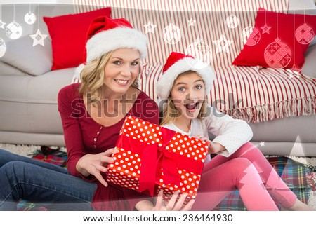 Festive mother and daughter smiling at camera with gifts against christmas themed frame