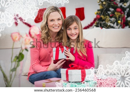 Festive mother and daughter with gift against snowflake frame - stock photo