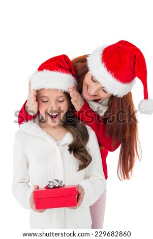 Festive mother surprising daughter with gift on white background