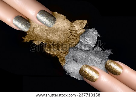 Festive nail art. Fingers with trendy gold and silver nail polish and crushed eye shadow with drops of water. Manicure and makeup concept. Closeup image isolated on black - stock photo