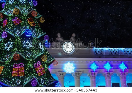 festive night city. decorated Christmas tree in the town square.  City clock on an old building.