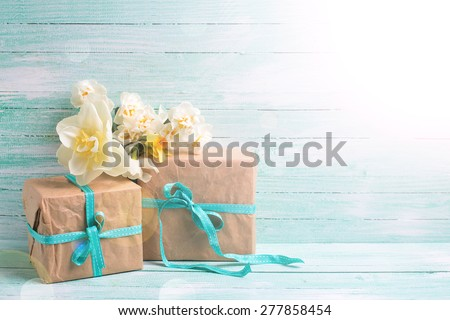 Festive present boxes  and flowers  in ray of light  on turquoise painted wooden background. Place for text. Selective focus. - stock photo