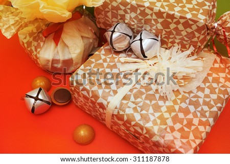 Festive present boxes with ribbon, candy and silver bells - stock photo