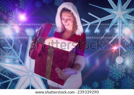 Festive pretty brunette opening a gift against digitally generated nightlife light design - stock photo