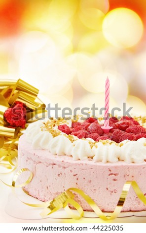 Festive raspberry cake with candle and ribbons. - stock photo