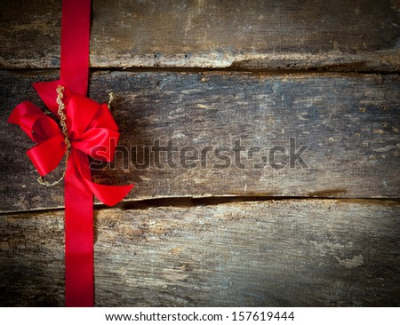 Festive red bow and ribbon forming a border for a Christmas card over rustic wooden planks with copyspace for your greeting or wishes - stock photo