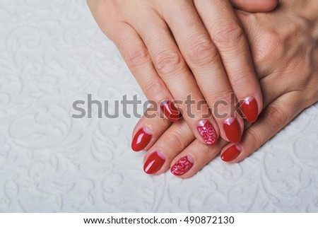 Festive red nail art on white clothe background