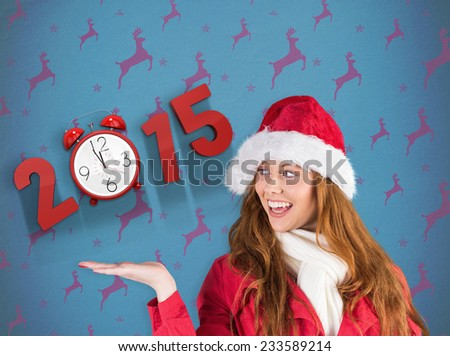 Festive redhead presenting with hand against blue and purple reindeer pattern - stock photo