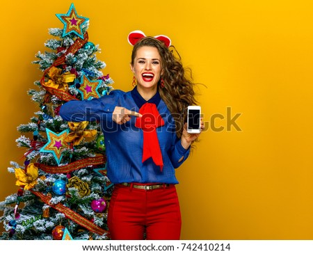 Festive season. happy stylish woman near Christmas tree on yellow background pointing at cellphone blank screen