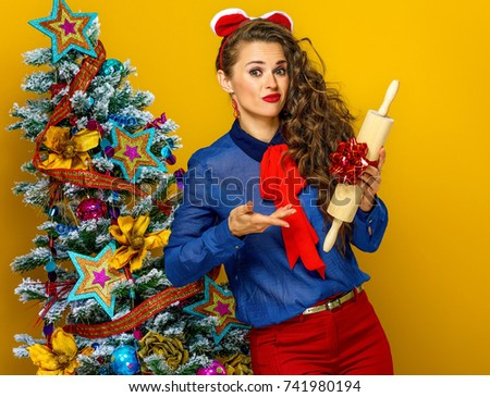 Festive season. young woman near Christmas tree isolated on yellow background unhappy with present