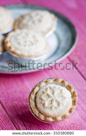 Festive shortcrust pastry mince pies. A sweet mince pie, a traditional rich festive food on pink wooden background. - stock photo