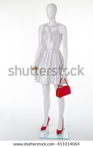 Festive silver dress on a white mannequin. Red patent-leather shoes and handbag.