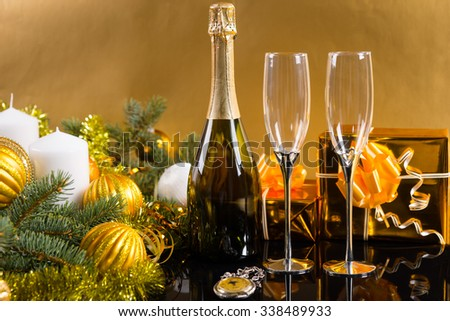 Festive Still Life - Antique Pocket Watch with Bottle of Champagne and Glasses in front of Golden Background with Gifts, Candles and Evergreen Decorated with Christmas Balls and Tinsel