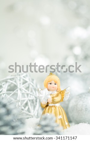 Festive Still Life - Delicate Golden Angel Figurine Holding Star and Standing Amongst Silver Christmas Decorations on Snowy Surface with Copy Space