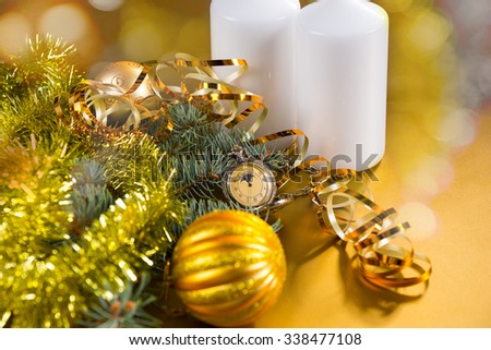 Festive Still Life of Antique Pocket Watch on Yellow Background with White Candles, Evergreens Decorated with Gold Christmas Balls, Tinsel Garland and Curled Ribbon - stock photo