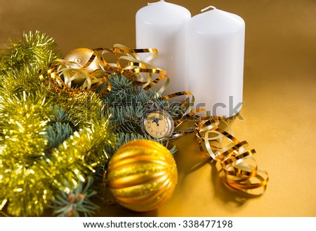 Festive Still Life of Antique Pocket Watch with Gold Ribbon, White Pillar Candles and Evergreen Branches Decorated with Gold Tinsel Garland and Christmas Balls - stock photo