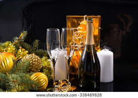 Festive Still Life of Bottle of Champagne with Elegant Glasses on Black Background with White Candles, Gold Wrapped Gifts and Evergreen Branches Decorated with Gold Christmas Balls and Tinsel - stock photo