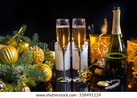 Festive Still Life - Two Glasses of Sparkling Champagne with Bottle, Candles, Gifts, Pocket Watch and Christmas Decorations on Black Background - stock photo